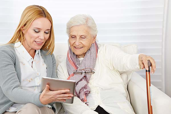 Accessibility - Woman sharing tablet with elderly lady
